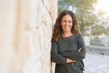 Beautiful middle age woman smiling cheerful leaning on a brick wall at the city street on a sunny...