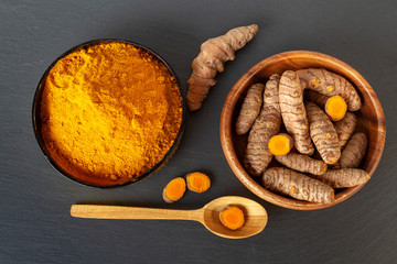 Turmeric roots and powder on gray slate background, overhead shot