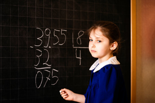 Italian elementary school girl trying to solve a mathematics examples, making a long division at blackboard
