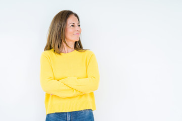 Wall Mural - Beautiful middle age woman wearing yellow sweater over isolated background smiling looking to the side with arms crossed convinced and confident