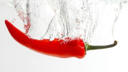 Fototapeta red chili pepper falling in water. healthy fresh vegetables and food. obraz