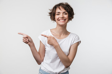 Portrait of cheerful woman with short brown hair in basic t-shirt rejoicing and pointing fingers at copyspace Wall mural