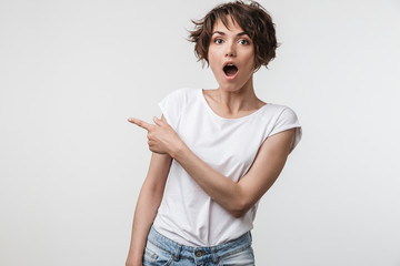 Portrait of beautiful woman with short hair in basic t-shirt rejoicing and pointing finger at copyspace Fototapete
