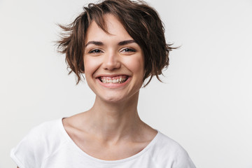 Portrait of kind woman with short brown hair in basic t-shirt smiling at camera