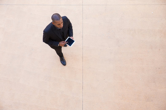 Successful businessman with tablet walking through office lobby. Top view of black man in formal suit using tablet and walking. Communication concept