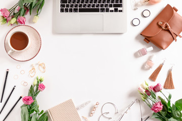 Workspace with laptop, mug of coffee, flowers, women's cosmetics and accessories on white background
