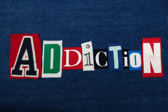 ADDICTION text word collage, colorful fabric on blue denim, abuse and treatment concept, horizontal aspect