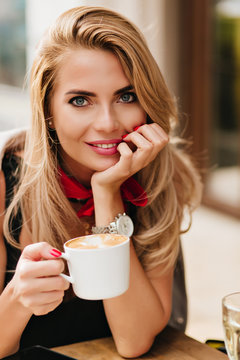 Close-up portrait of attractive young woman with deep blue eyes propping face with hand and smiling on blur background. Graceful lady holding cup of tea posing during dinner in cafe.