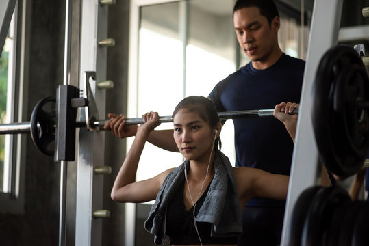 attractive woman doing exercise with personal trainer at gym