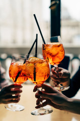 Group of friends cheers with aperol spritz