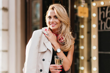 Excited blonde woman in trendy silver wristwatch posing with pleasure in her birthday, holding wineglass. Charming girl with tanned skin drinking champagne and having fun in weekend. Wall mural