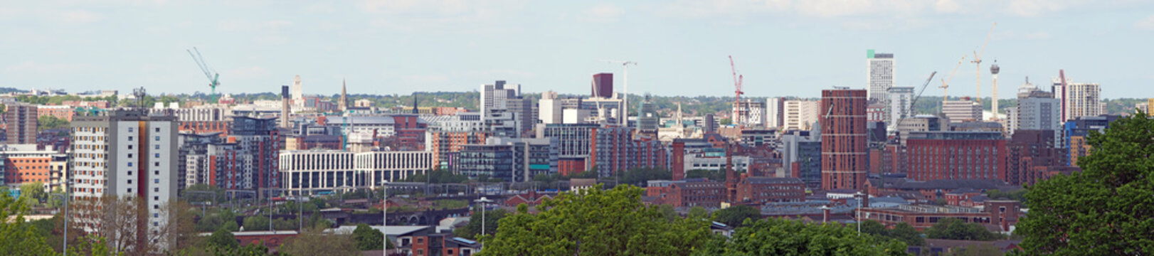 a wide panoramic view showing the whole of leeds city center with towers apartments roads and commercial buildings against a blue sky