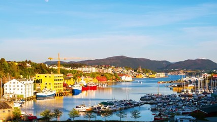 Wall Mural - Kristiansund, Norway. Aerial view of the city center of Kristiansund, Norway during the sunny day. Time-lapse of a port with historical buildings, mountains at the background, zoom in