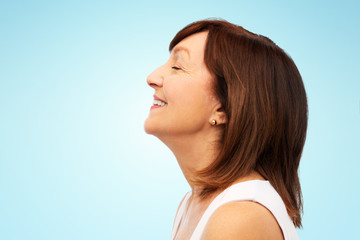 beauty, rhinoplasty and old people concept - profile of smiling senior woman over blue background