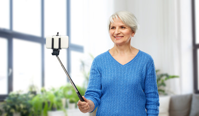technology and old people concept - smiling senior woman taking picture by smartphone on selfie stick over home living room background