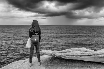Black and white view of a girl observing the sea with a lot of wind and cloudy sky