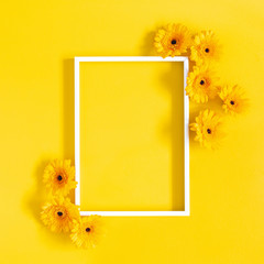 Flowers composition. Yellow gerbera flowers, photo frame on yellow background. Flat lay, top view, copy space