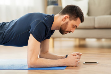 sport, fitness and healthy lifestyle concept - man looking at smartphone and doing plank exercise at home Fototapete