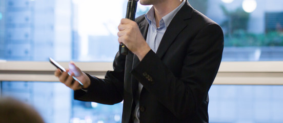 Speaker holding microphone in conference. Corporate executive giving speech during business training seminar. Expert presenter on stage during lecture. CEO presenting investor pitch.