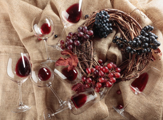 Red wine and grapes on a table covered with burlap.