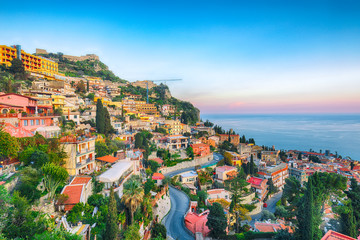 Aquamarine blue waters of  sea and fantastic cityscape of Taormina during sunset Wall mural