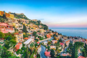 Aquamarine blue waters of  sea and fantastic cityscape of Taormina during sunset Fototapete