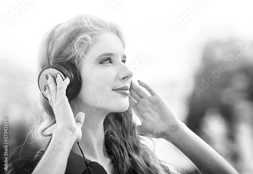 Girl in headphones listens to mp3 music in city  Black and