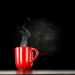Wall Mural - Red mug on black background of free space