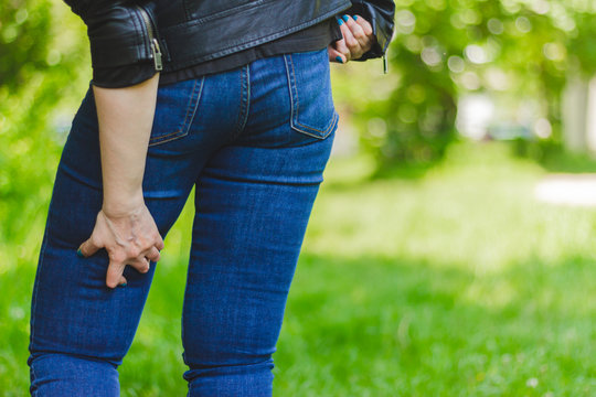 Young woman wearing jeans and leather jacket holding her painful upper leg while walking in nature – Girl massaging her inflamed and spasmed muscles