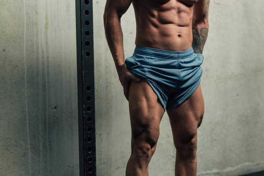 Young strong man posing and flexing his quadriceps legs muscles
