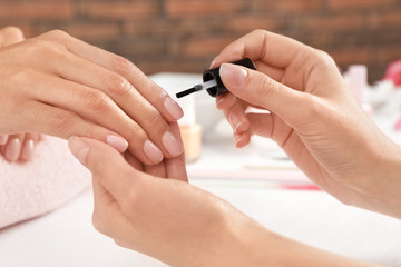 Poster de jardin Manicure Manicurist applying polish on client's nails at table, closeup. Spa treatment