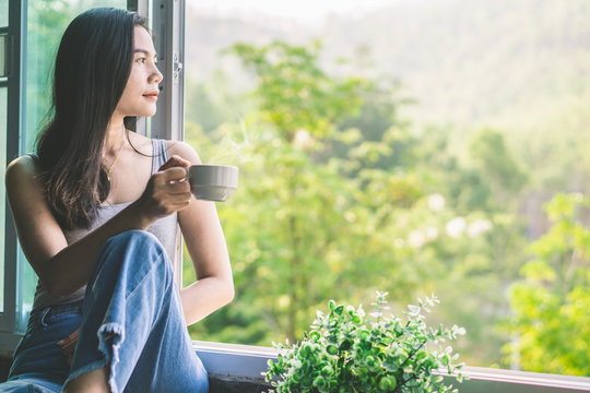 beautiful Asian woman sitting next to the window drinking coffee and relaxing with beautiful nature view