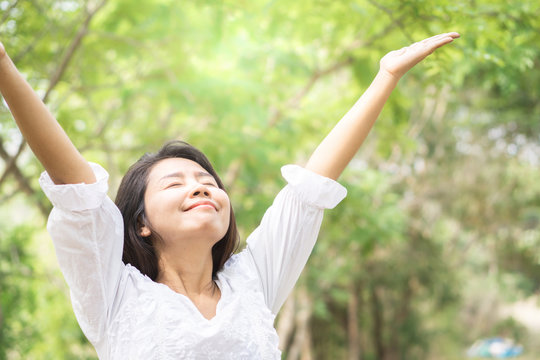happy Asian woman arms up and breathing deep outdoors with nature background