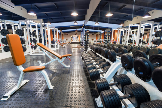 New fitness machines and dumbbells in modern gym interior
