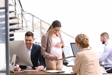 Young pregnant woman working with her employees in office