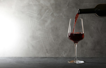 Spoed Foto op Canvas Alcohol Pouring red wine from bottle into glass on table. Space for text