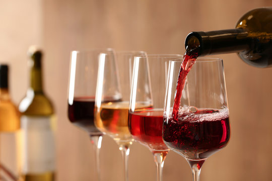 Pouring wine from bottle into glass on blurred background, closeup