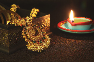 Fototapete - Indian Traditional Gold  Lakshmi Pendant Necklace with Oil Lamp