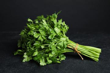 Bunch of fresh green parsley on dark table