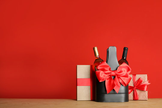 Bottles of wine in holder with bow and gift boxes on table against color background. Space for text