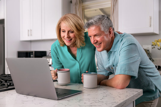 Happy senior couple retired at home enjoying the internet together, smiling laughing and cheerful.