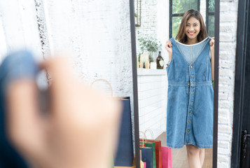 Young Asian attractive woman trying on a blue jean dress in a fashion store, looking at her reflection in a mirror. Shopping, fashion, clothes, style and people concept