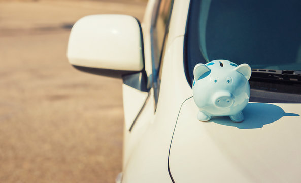 Piggy money bank on the hood of a new white car