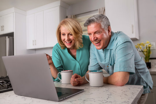 Grandparents on computer communicating with grandkids via video chat from home kitchen