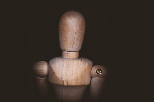 Wooden Human Manikin posing on a black background.