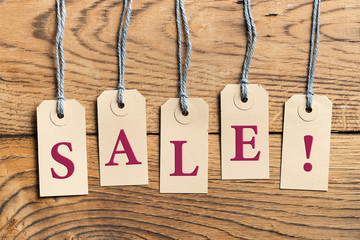 Hangtags with the word SALE! on wooden background