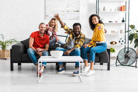 Happy laughing multicultural young people sitting on couch and spending time together