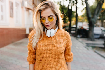 Dreamy fair-haired young lady in yellow sweater looking down standing on blur street background. Outdoor portrait of european female model in headphones posing with tired smile. Wall mural
