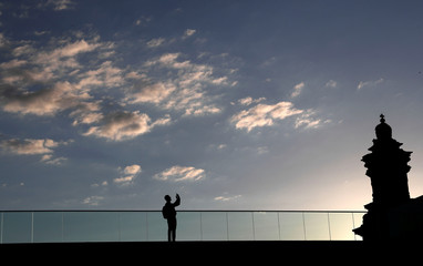 A man takes pictures with his mobile device on the roof of the lower house of parliament, Bundestag, at the Reichstag's building in Berlin