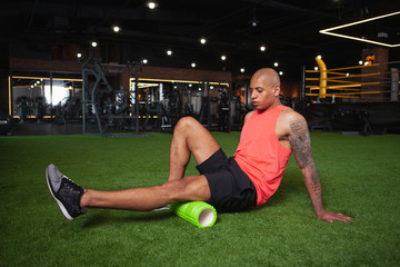Attractive young African male athlete relaxing leg muscles after gym workout, using foam roller. Athletic handsome man resting after exercising, using foam roller. Relaxation, pain relief concept